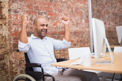 Casual businessman in wheelchair cheering at his desk Stock Photos