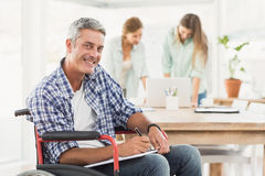 Casual businessman in wheelchair with notepad Stock Image