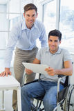 Casual businessman in wheelchair smiling at camera with colleague Royalty Free Stock Image