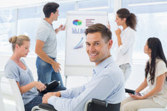 Casual businessman in wheelchair smiling at camera during presentation Royalty Free Stock Photos