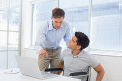 Casual businessman in wheelchair talking with colleague using laptop. In the office Royalty Free Stock Images