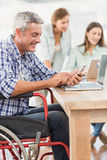 Casual businessman in wheelchair using smartphone Royalty Free Stock Image