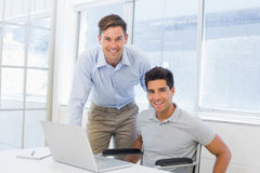 Casual businessman in wheelchair working at his desk with colleague Royalty Free Stock Photo