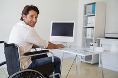 Casual businessman in wheelchair working at his desk stock photos