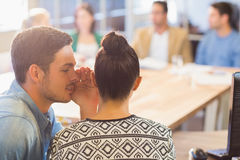 Casual businessman whispering secret to his colleague. In the office Stock Photos