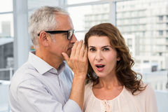Casual businessman whispering secret to his colleague Stock Photo