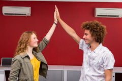 Casual businessman and woman high fiving Stock Photo
