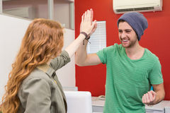 Casual businessman and woman high fiving Royalty Free Stock Image