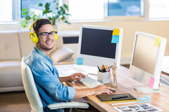 Casual businessman working at his desk and listening music Stock Photography
