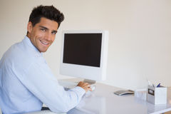Casual businessman working at his desk smiling at camera Stock Image