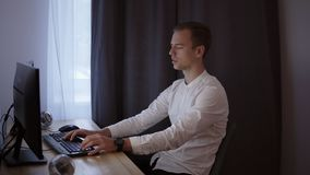 Casual businessman working at home, sitting at desk, typing on keyboard, looking at computer screen.Grey curtain on the. Background stock video footage