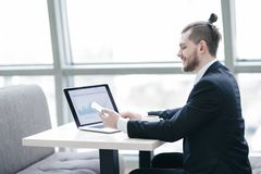 Casual businessman working with mobile and laptop in modern office. Photo with copy space stock photography