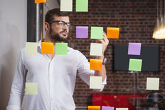 Casual businessman writing on sticky notes Stock Photo