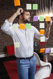 Casual businessman writing on sticky notes Stock Photos