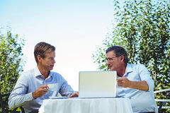 Casual businessmen having coffee and using laptop Royalty Free Stock Image