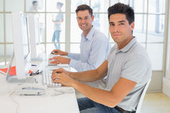 Casual businessmen smiling at camera at desk Stock Photo