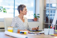 Casual businesswoman drawing with digitizer Royalty Free Stock Image