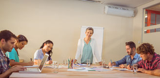 Casual businesswoman giving presentation to her colleagues Stock Images