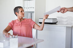 Casual businesswoman handing document to colleague Stock Photography