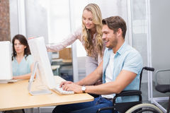 Casual businesswoman helping colleague in wheelchair Stock Photo