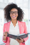 Casual businesswoman holding her diary smiling at camera Stock Photos