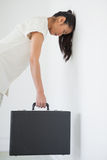 Casual businesswoman leaning against wall with briefcase Royalty Free Stock Photography