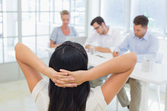 Casual businesswoman leaning back during a meeting Stock Images