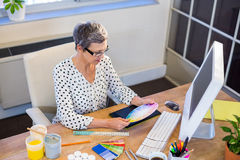 Casual businesswoman looking at colour chart Royalty Free Stock Images