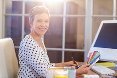 Casual businesswoman looking at colour swatch and drawing with digitizer Stock Image