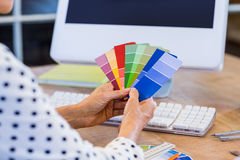 Casual businesswoman looking at colour swatch Royalty Free Stock Photography