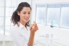 Casual businesswoman looking at her electronic cigarette Royalty Free Stock Photos