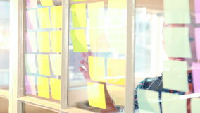 Casual businesswoman looking at post it