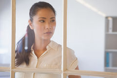 Casual businesswoman looking through window Stock Photos