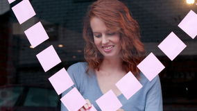 Casual businesswoman putting sticky notes on glass stock video footage