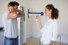 Casual businesswoman shouting at colleague through megaphone Stock Photography