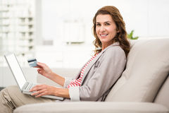 Casual businesswoman sitting on couch and ordering online. Portrait of casual businesswoman sitting on couch and ordering online in the office Royalty Free Stock Image