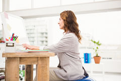 Casual businesswoman sitting on exercise ball while working Royalty Free Stock Photo