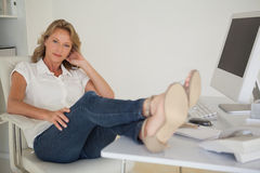 Casual businesswoman sitting at her desk with feet up Stock Photos