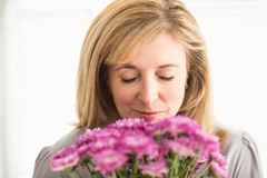 Casual businesswoman smelling at flowers Stock Photo