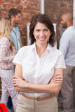 Casual businesswoman smiling at camera with arms crossed Stock Photography
