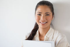 Casual businesswoman smiling at camera holding folder Royalty Free Stock Photo