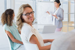 Casual businesswoman smiling at camera during meeting Stock Photo