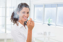 Casual businesswoman smoking an electronic cigarette Royalty Free Stock Image