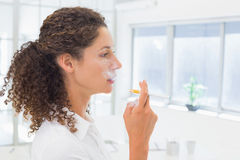Casual businesswoman smoking an electronic cigarette Royalty Free Stock Photography