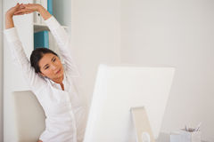 Casual businesswoman stretching at her desk Royalty Free Stock Photography