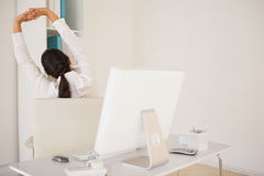 Casual businesswoman stretching at her desk Royalty Free Stock Photo