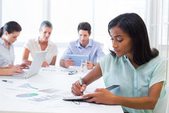 Casual businesswoman taking notes during meeting Stock Image