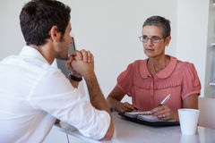 Casual businesswoman talking with colleague Stock Images
