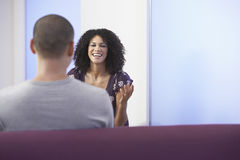 Casual Businesswoman Talking To Colleague. Casually dressed businesswoman talking to colleague in office Stock Photo