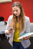 Casual businesswoman text messaging in office Stock Image